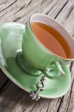 Green antique tea cup with healthy organic tea Stock Photo