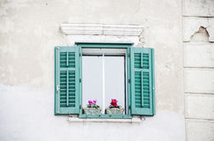 Green antique window with pot flowers. Antique window with green shutters and pot flowers royalty free stock image
