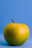 Green aple. Green apple against blue background Stock Image
