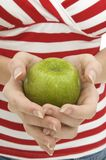 Green Apple. A young woman holding a green apple Royalty Free Stock Image