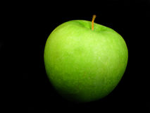 Green Apple. Single green apple isolated on a black background Stock Photos