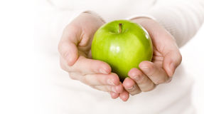 Green Apple. Womans hands holding a grannysmith green apple royalty free stock photography
