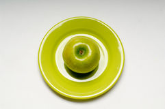 Green apple. On green plate Stock Photos
