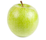 Green Apple. Isolated frontal shot of a fresh green apple with stem and drops of water on it Royalty Free Stock Photos