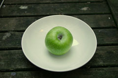 Green apple. On a white plate Royalty Free Stock Photo
