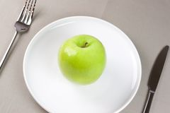 Green apple. Grenn apple on white plate with knife and fork Royalty Free Stock Photos