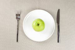 Green apple. On white plate with knife and fork Stock Image