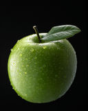 Green apple. With single leaf on dark background royalty free stock photography