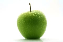 Green apple. Close up of a green apple covered in water droplets royalty free stock photo