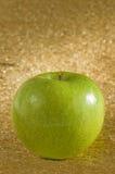 Green apple. On a golden surface Stock Photos