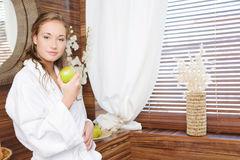 A green apple. The beautiful girl holds a green apple royalty free stock photography