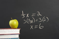 Green apple and algebra equation. An apple on stack of books by an algebra equation on the blackboard royalty free stock photos
