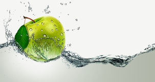 Green Apple amid splashing water. Royalty Free Stock Photography