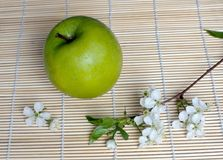 Green apple and apple blossom. On bamboo mat Royalty Free Stock Photos