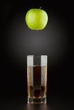 Green apple and apple juice into a faceted transparent glass Stock Photos