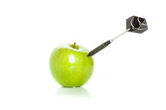 Green apple as a target for black steel dart Royalty Free Stock Images