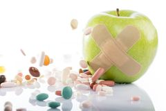 Green apple with a band-aid and varios pills Royalty Free Stock Photos