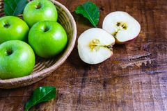 .Green apple in a basket on a wooden table royalty free stock photo