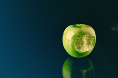 Green apple with big bite. Green apple over blue reflective surface and a big bite at ine side, lots of negative space for copy and composition, nice reflection stock images