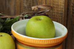 Green apple. Big green apple in yellow ceramic bowl Stock Image