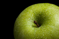 Green apple on black background. Fresh wet green apple on black background Stock Image