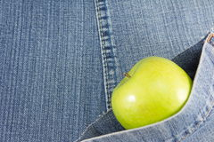 Green apple in blue jeans pocket Royalty Free Stock Photo