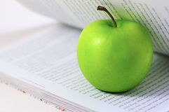 Green apple in a book royalty free stock photo