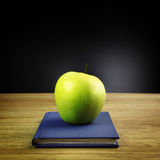 Green apple on book Royalty Free Stock Photos