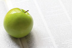 Green apple on a book Stock Image