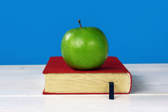 Green apple on book with red cover Stock Images