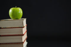 Green apple on book stack against black background Stock Photos