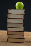 Green apple on book stack against black background Stock Photography