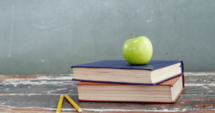 Green apple on book stack. With pencil on tbale stock video footage