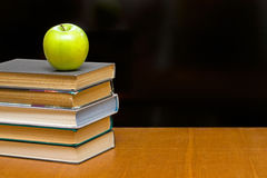 Green apple and  books on the desk. Blackboard as background Stock Images