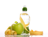 Green apple, bottle with aqua and small grapes Royalty Free Stock Photo