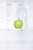 A green apple and bottles of water in a fridge Royalty Free Stock Photos