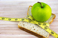Green apple and bread with tape measure on wood Royalty Free Stock Images