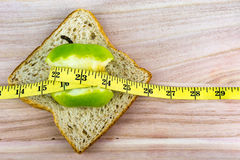 Green apple and bread with tape measure on wooden surface Royalty Free Stock Images