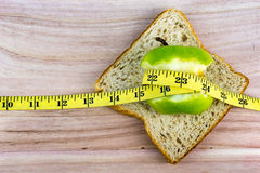 Green apple and bread with tape measure on wooden surface Royalty Free Stock Photo