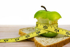 Green apple and bread with tape measure on wooden surface. Stock Images