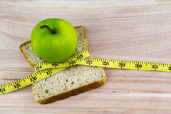 Green apple and bread wrapped with measuring tape on wooden surface. Stock Photos