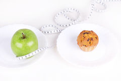 Green apple and cakes with measureing tape Royalty Free Stock Image