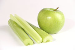 Green apple and celery stems Royalty Free Stock Photography