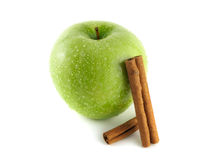 Green apple with cinnamon pods on white. Wet green apple with cinnamon pods (white background). Fresh diet fruit. Healthy fruit with vitamins Stock Image
