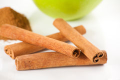 Green apple, cinnamon on white plate Stock Photos