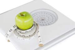 Green apple circled with a tape measure Stock Images