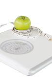 Green apple circled with a tape measure Royalty Free Stock Photos
