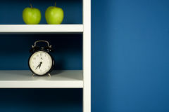Green apple and clock inside white bookcase stock photography