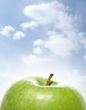 Green apple on a cloudy background. Green and tasty apple on a cloudy background royalty free stock image