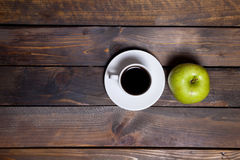 Green apple and coffee in white cup on wooden background Stock Image